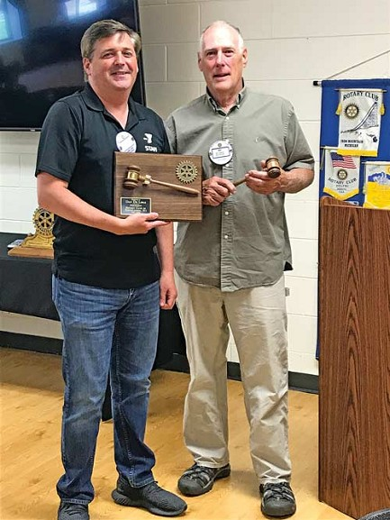 Submitted photographsTop: Dan De Lisle (left), president of Rhinelander Rotary from July 2017 - 2019, and new club president Kim Zambon pose together. De Lisle, holding the plaque that was given to him in appreciation of his service, presented Zambon with a gavel as a symbol of his new office. Bottom: Zambon and and Axel Besse, a Rotary youth exchange student from Le Puy en Velay, France, exchange Rotary Club flags.